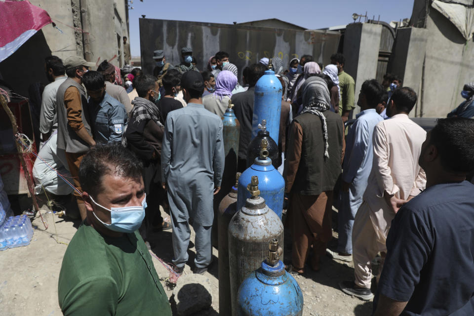 Men wait outside a privately owned oxygen factory to get their oxygen cylinders refilled, in Kabul, Afghanistan, Saturday, June 19, 2021. Health officials say Afghanistan is fast running out of oxygen as a deadly third surge of COVID worsen. (AP Photo/Rahmat Gul)