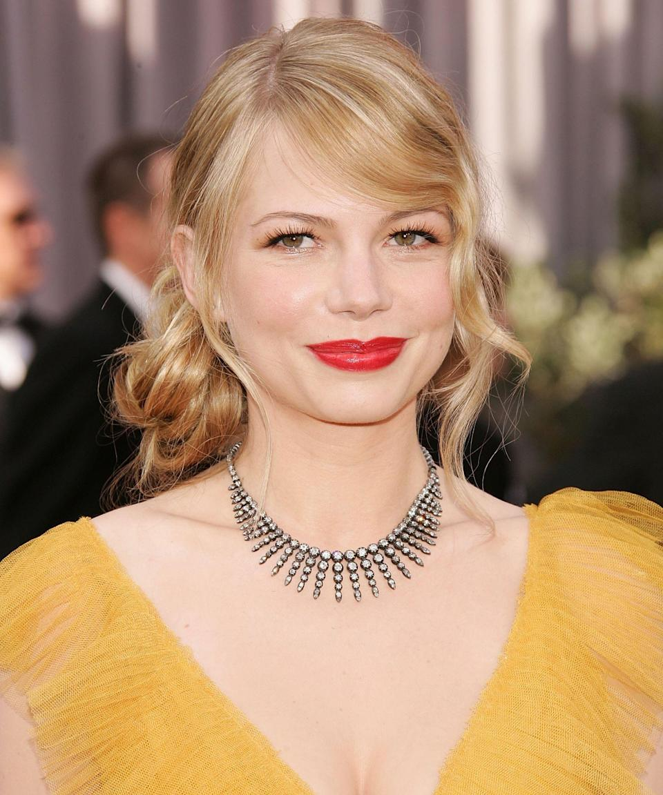 """<p><strong>Michelle Williams, 2006</strong></p><p>The timeless pairing of <a href=""""https://www.refinery29.com/en-us/matching-makeup-clothes#slide-2"""" rel=""""nofollow noopener"""" target=""""_blank"""" data-ylk=""""slk:matte red lipstick with a mustard-yellow dress"""" class=""""link rapid-noclick-resp"""">matte red lipstick with a mustard-yellow dress</a> tends to get the credit for this iconic beauty look, and for good reason... but Michelle's hair! The bafflingly undone, yet Oscar-worthy updo, thanks in part to perfectly-shaped bangs and face-framing pieces, is one for the books.</p><span class=""""copyright"""">Photo: Frazer Harrison/Getty Images.</span>"""