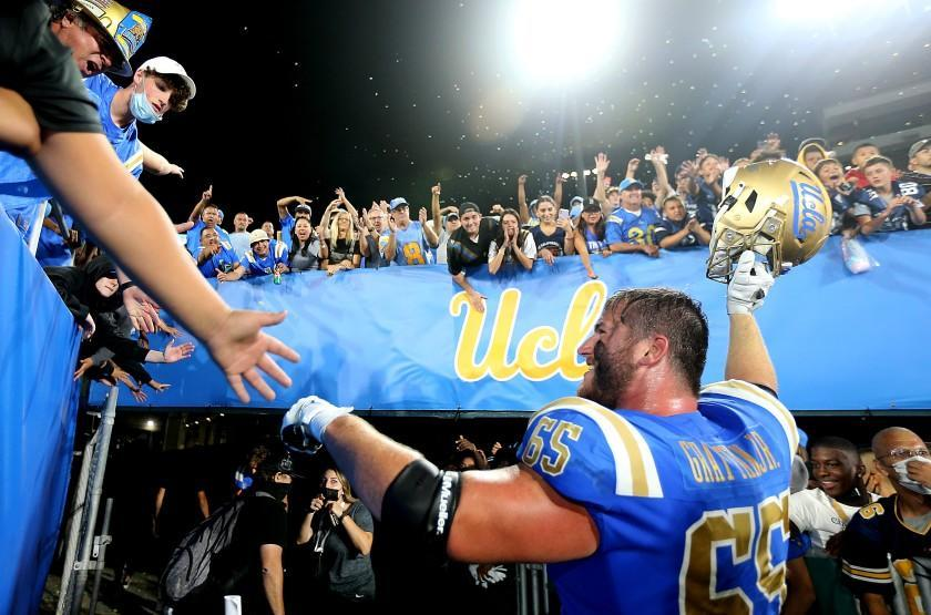 PASADENA, CALIF. - SEP. 4, 2021. Bruins starting left guard Paul Grattan is cheered by fans after UCLA beat LSU, 38-27, at the Rose Bowl on Saturday, Sept. 1, 2021. (Luis Sinco / Los Angeles Times)