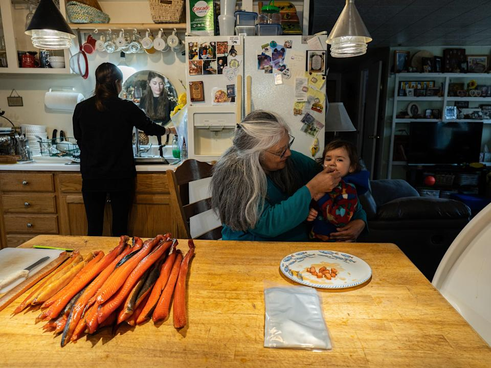 Pam Smith feeds her 20-month-old grandson, Galushia Smith, smoked king salmon—the first of the season—in her home kitchen while her daughter-in-law, Holly Smith, washes her hands in preparation to help process and package it.
