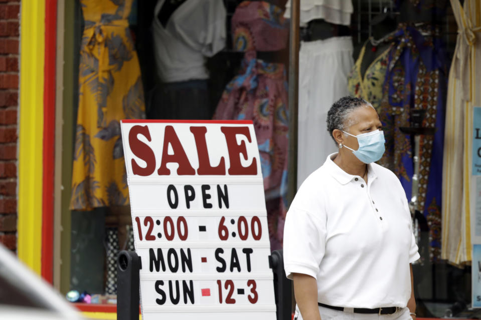 A woman walks past a boutique with a sale sign, Thursday, June 4, 2020, in Cleveland Heights, Ohio. The state says more than 34,000 Ohioans filed unemployment claims during the last week of May. That is the lowest figure since Ohio's stay-at-home orders depressed the economy and led to widespread layoffs. (AP Photo/Tony Dejak)