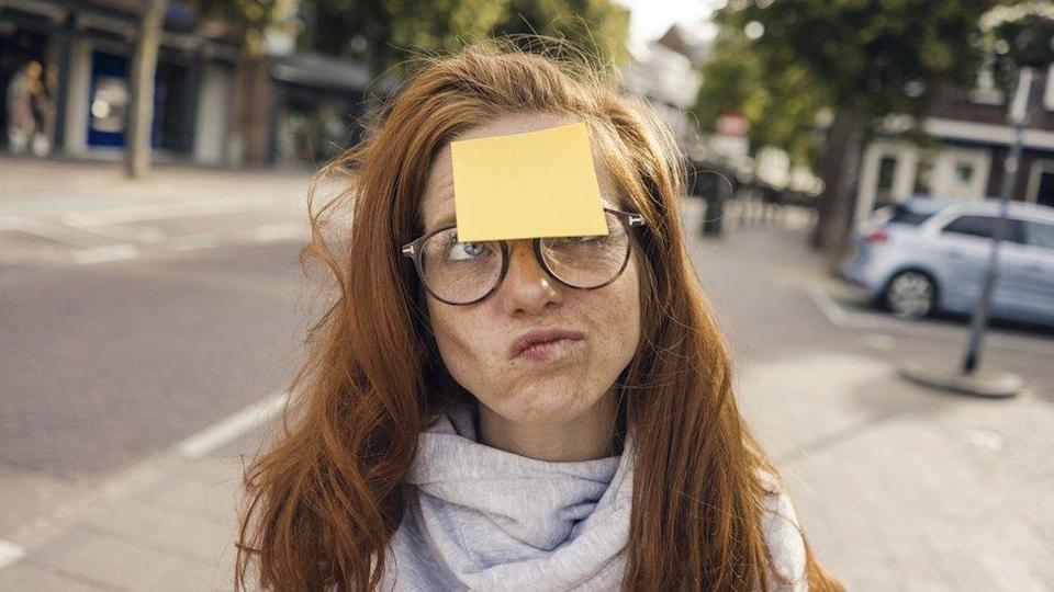 Woman on the street, with a post-it note stuck to her forehead