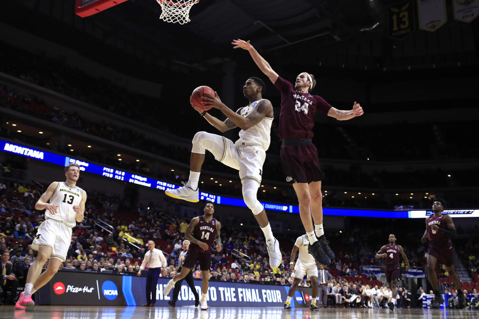 <p>Charles Matthews #1 of the Michigan Wolverines attempts a shot past Bobby Moorehead #24 of the Montana Grizzlies in the second half during the first round of the 2019 NCAA Men's Basketball Tournament at Wells Fargo Arena on March 21, 2019 in Des Moines, Iowa. </p>