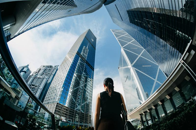 Rear view of professional young businesswoman standing against contemporary financial skyscrapers in downtown financial district and looking up into sky with positive emotion