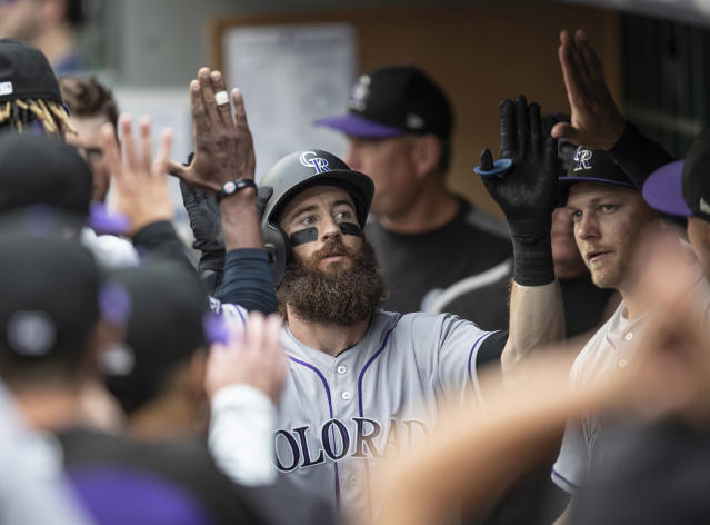 Colorado Rockies' Charlie Blackmon is congratulated by teammates in the dugout after hitting a solo home run off of Seattle Mariners starting pitcher Felix Hernandez during the first inning of a baseball game, Friday, July 6, 2018, in Seattle. The Rockies won 7-1. (AP Photo/Stephen Brashear)
