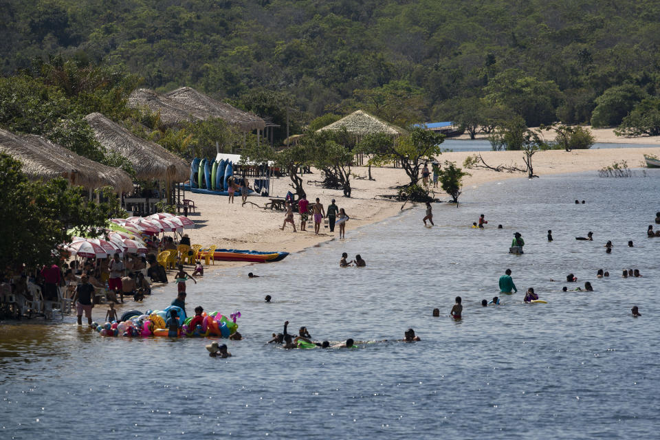 People swim in Alter do Chao, district of Santarem, Para state, Brazil, Thursday, Aug. 27, 2020. One of Brazil's trendiest destinations, Alter do Chão welcomes up to 100,000 visitors each year in the high season, though considerably less in 2020 because of the COVID-19 pandemic. (AP Photo/Andre Penner)