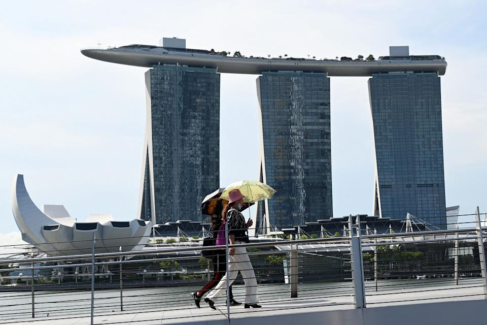 People seen walking across a bridge near the Marina Bay Sands integrated resort on 14 April, 2021. (PHOTO: AFP via Getty Images)