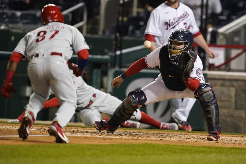 Washington Nationals catcher Alex Avila catches the throw from left fielder Kyle Schwarber before making the tag on Philadelphia Phillies' Odúbel Herrera for the out during the fifth inning of a baseball game at Nationals Park, Wednesday, May 12, 2021, in Washington. (AP Photo/Alex Brandon)