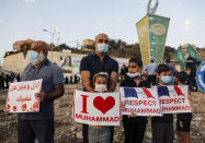 Arab Israeli Muslim demonstrators (including children), clad in masks due to the COVID-19 coronavirus pandemic, hold up signs as they gather for a rally protesting against the comments of French President Emmanuel Macron over Prophet Mohammed cartoons, in the Arab town of Umm-Al Fahem in Northen Israel on October 25, 2020. (Photo by Ahmad GHARABLI / AFP) (Photo by AHMAD GHARABLI/AFP via Getty Images)