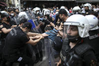 Protesters are detained by police in central Istanbul, Saturday, June 26, 2021. Police used tear gas to disperse the crowds and detained dozens of LGTBI activists as hundreds defied a ban and tried to stage a gay pride event. (AP Photo/Emrah Gurel)