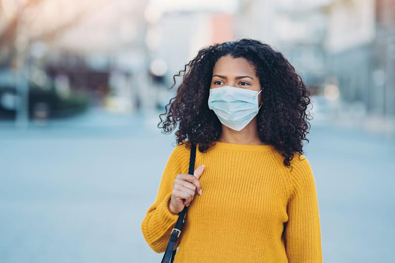 Wearing a mask and staying away from other people will likely be a part of Canadians' lives for many more months. (Photo: pixelfit via Getty Images)