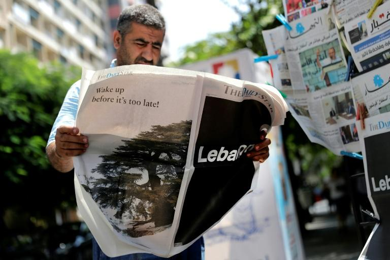 """A man checks a copy of the Lebanese local English-language newspaper """"The Daily Star"""" that ran no news articles in its print edition today in protest at the """"deteriorating situation"""" in Lebanon"""