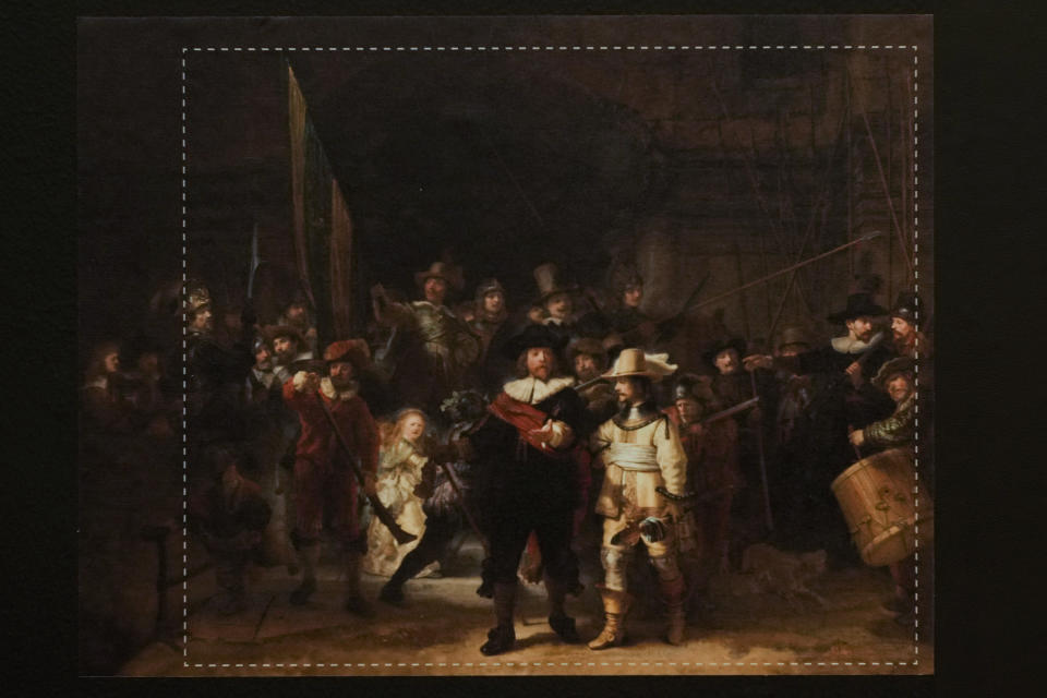 A photograph with lines showing the added parts explains how Rembrandt's biggest painting the Night Watch just got bigger with the help of artificial intelligence in Amsterdam, Netherlands, Wednesday, June 23, 2021. The Dutch national museum and art gallery reveals findings from a long-term project to examine in minute detail Rembrandt van Rijn's masterpiece the Night Watch.(AP Photo/Peter Dejong)