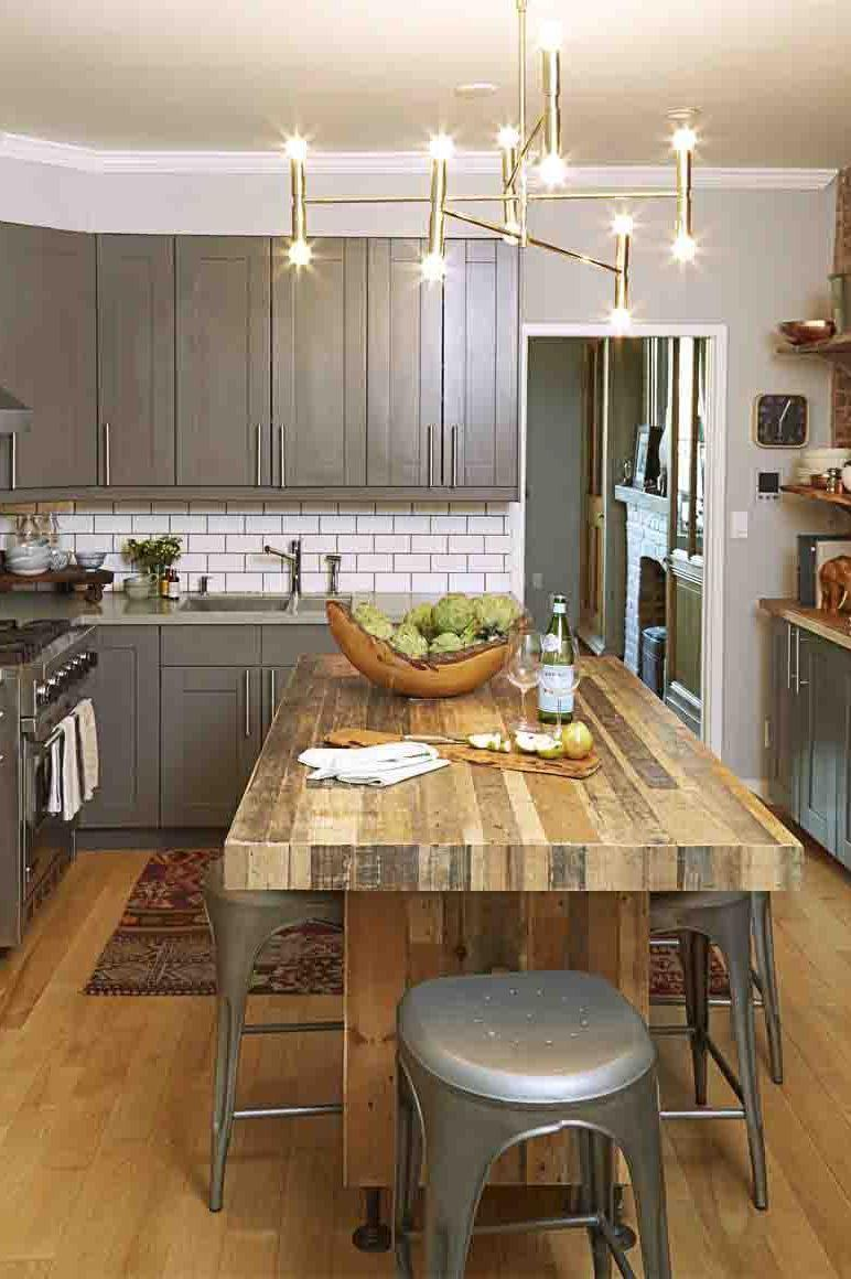 <p>A white subway tile backsplash balances this kitchen's deep gray cabinets and wood island. </p>