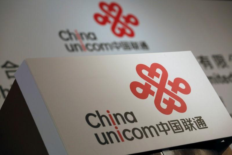 FILE PHOTO - Company logos of China Unicom are displayed at a news conference during the company's announcement of its annual results in Hong Kong