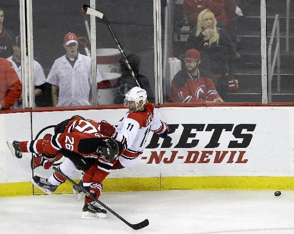 New Jersey Devils left wing Patrik Elias (26), of the Czech Republic, and Carolina Hurricanes center Jordan Staal (11) collide while competing for the puck during the third period of an NHL hockey game, Wednesday, Nov. 27, 2013, in Newark, N.J. The Hurricanes won 4-3. (AP Photo/Julio Cortez)
