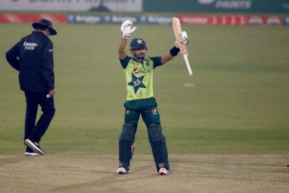 Pakistan's Mohammad Rizwan, center, raise bat to celebrate his fifty during the 2nd Twenty20 cricket match between Pakistan and South Africa at the Gaddafi Stadium, in Lahore, Pakistan, Saturday, Feb. 13, 2021. (AP Photo/K.M. Chaudary)