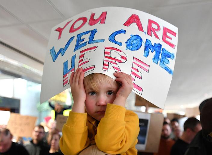 <p>Hattie Burke-Foreuic holds up a sign while sitting on her father's shoulders during a protest at San Francisco International Airport, Jan. 29, 2017. (Photo: Josh Edelson/AFP/Getty Images) </p>