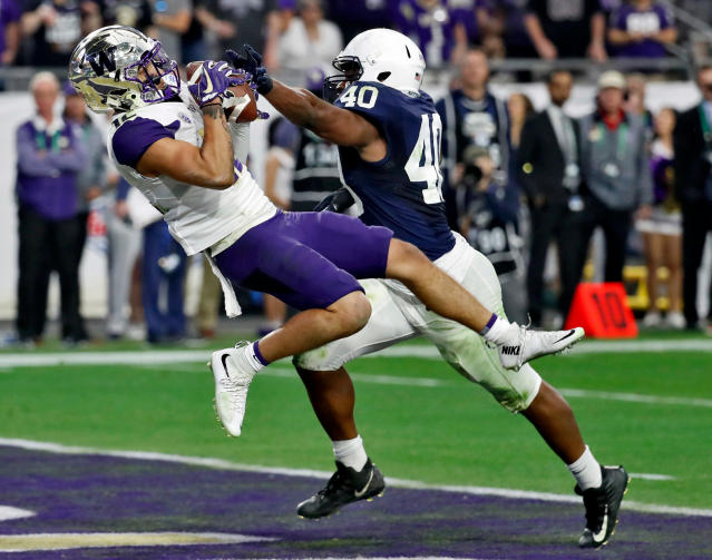 FILE - In this Dec. 30, 2017, file photo, Washington wide receiver Aaron Fuller (12) pulls in a touchdown pass as Penn State linebacker Jason Cabinda (40) defends during the second half of the Fiesta Bowl NCAA college football game, in Glendale, Ariz. The Huskies need someone to replace Dante Pettis, their top pass-catcher from a year ago. Fuller showed flashes during his first two seasons, including six catches in the Fiesta Bowl, and emerged as one of QB Jake Browning's top targets during the spring. (AP Photo/Rick Scuteri, File)