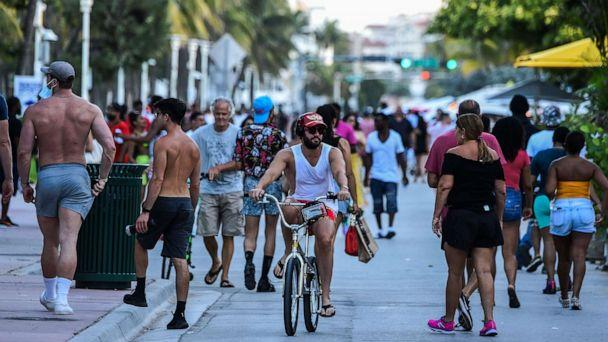 PHOTO: A man rides a bicycle as people walk on Ocean Drive in Miami Beach, Florida on June 26, 2020. (Chandan Khanna/AFP via Getty Images)