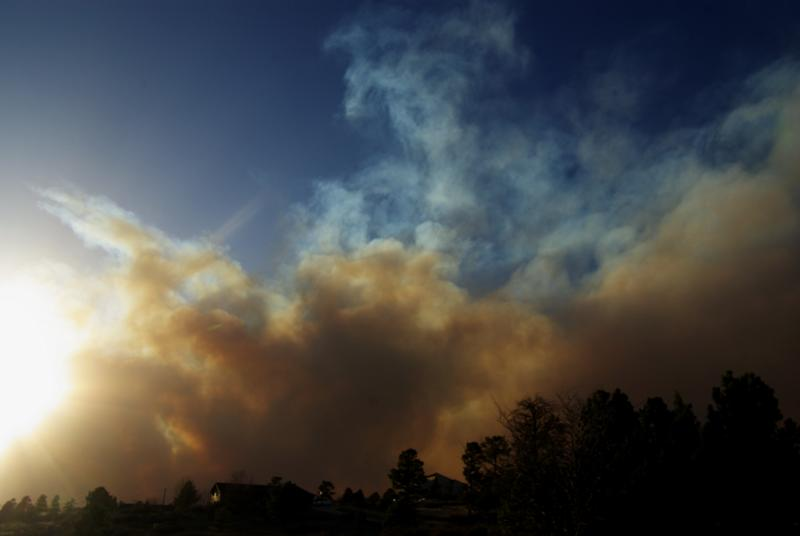 In this photo provided by Kris Garrett, A plume of smoke rises skyward over the top of a wildfire burning out of control near Conifer, Colo., on Monday, March 26, 2012. High winds fanned the fire and kept air craft from being used to knock the fire down. (AP Photo/Kris Garrett)