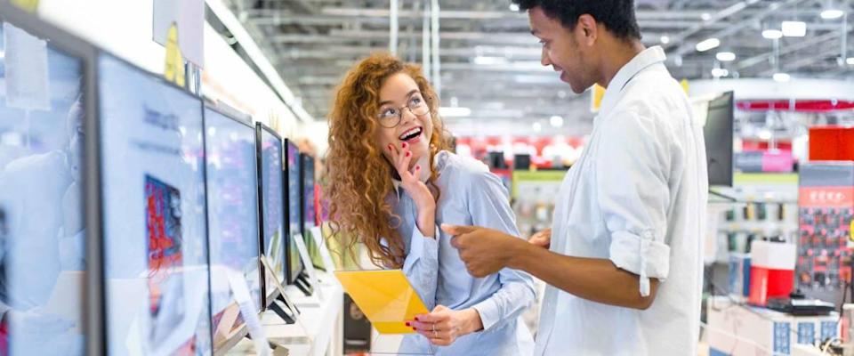 African guy with red-haired girl standing in front of the stand in the electronics store choose a plasma TV looking at the price tags