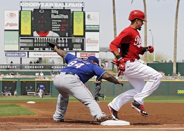 Cincinnati Reds' Billy Hamilton beats the throw to Texas Rangers first baseman Prince Fielder (84) for an infield single in the first inning of a spring exhibition baseball game Thursday, March 20, 2014, in Goodyear, Ariz. (AP Photo/Mark Duncan)