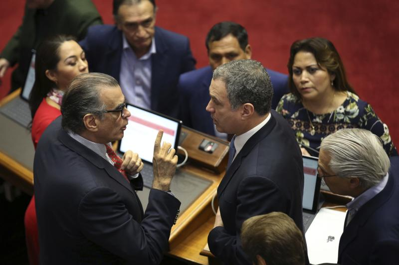 Flanked by lawmakers, President of the Peruvian Congress Pedro Olaechea, left, and Prime Minister Salvador del Solar, have a discussion inside the Congress building in Lima, Peru, Monday, Sept. 30, 2019. The political duel between Peruvian President Martin Vizcarra and Congress intensified in recent weeks after lawmakers decided to shelve Vizcarra's proposal to hold early presidential and congressional elections, which he argues is necessary to break the deadlock and stabilize the nation.  (AP Photo/Martin Mejia)