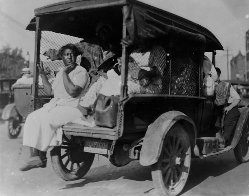 A woman seated on the back of a small truck loaded with people during the 1921 Tulsa race massacre. (Photo: Historical via Getty Images)
