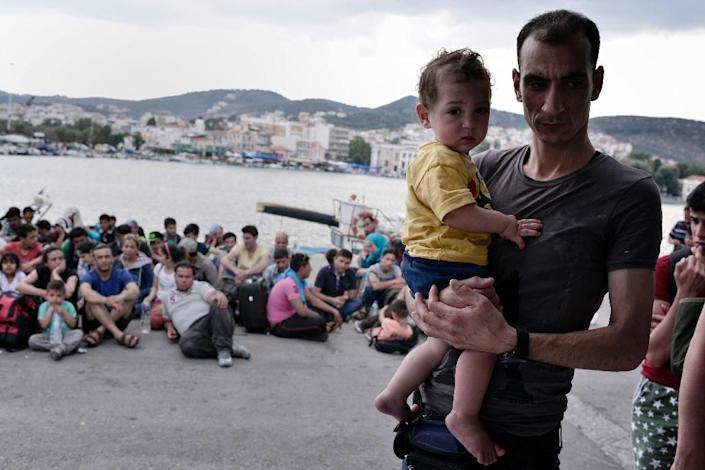 Syrian refugees who arrived early on June 18, 2015 to the Greek island of Lesbos wait to be registered at the port of Mytilini (AFP Photo/Louisa Gouliamaki)