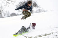 Aidin Weber, 18, of Clarkston, Wash., leaps over his younger brother, David, 13, as he sleds down a hill at Sunset Park in Lewiston, Idaho, on Friday, Feb. 12, 2021. (Pete Caster/Lewiston Tribune via AP)