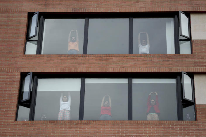 Residents take part in an aerobics class led by city police instructing from the street below during a lockdown ordered by the government in an effort to prevent the spread of the new coronavirus, in Bogota, Colombia, Friday, April 3, 2020. Colombian police visit neighborhoods inviting residents to their windows or balconies to participate in an aerobics class, and encourage social distancing. (AP Photo/Fernando Vergara)