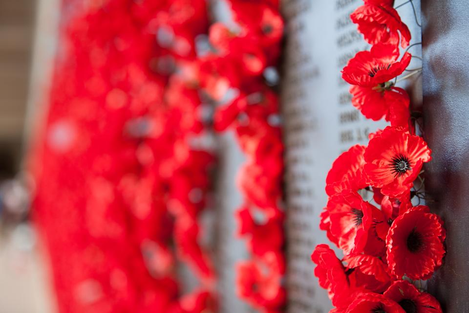 Close up of red poppies on a war memorial.
