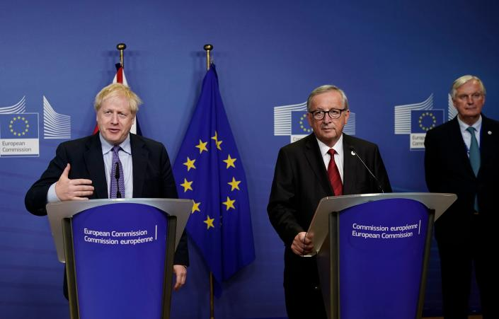 British Prime Minister Boris Johnson (L) is watched by President of the European Commission Jean-Claude Juncker (C) and EU chief Brexit negotiator Michel Barnier (R) as they address a press conference at a European Union Summit at European Union Headquarters in Brussels on October 17, 2019. (Photo by Kenzo TRIBOUILLARD / AFP) (Photo by KENZO TRIBOUILLARD/AFP via Getty Images)