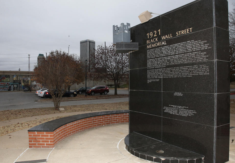 FILE - In this Dec. 15, 2016 file photo, a memorial to Tulsa's Black Wall Street sits outside the Greenwood Cultural Center on the outskirts of downtown Tulsa, Okla. A once-prosperous section of Tulsa that became the site of one of the worst race riots in American history is attempting to remake itself again after decades of neglect. G.T. Bynum mayor of Tulsa said on Tuesday, Oct. 2, 2018, he plans to re-examine whether mass graves hold remains of those killed in one of the nation's worst race massacres nearly 100 years ago. (AP Photo/Sue Ogrocki, File)