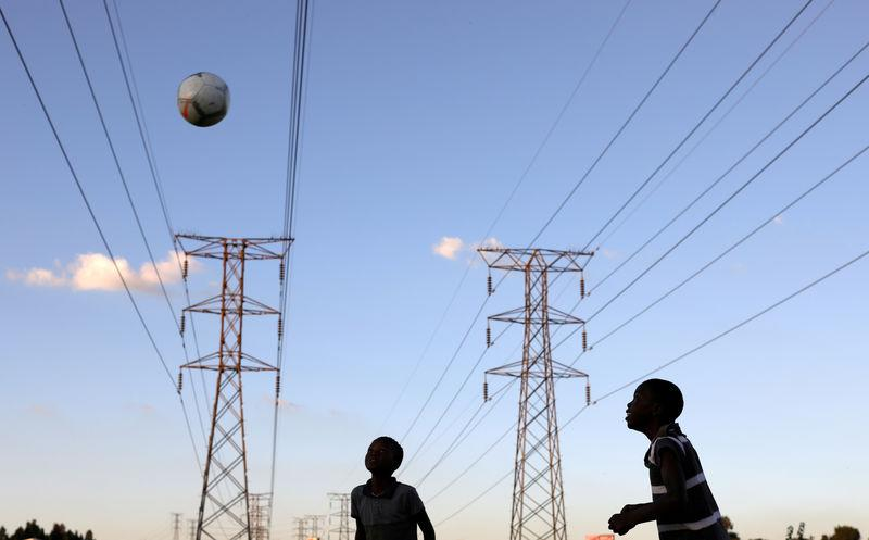 FILE PHOTO: Boys play soccer below electricity pylons in Soweto