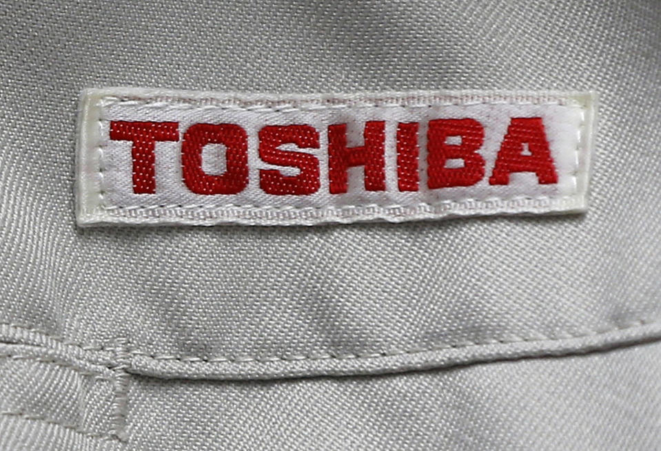 """FILE - In this Thursday, June 15, 2017, photo, the logo of Toshiba Corp., Japan's electronics and energy company, is seen on a worker's jacket in Yokosuka, near Tokyo. Toshiba Corp. has brushed off a new missive from CVC Partners about the global fund's interest in acquiring the Japanese manufacturer. Toshiba said Tuesday that a letter from CVC was """"not possible to evaluate."""" (AP Photo/Shuji Kajiyama, File)"""