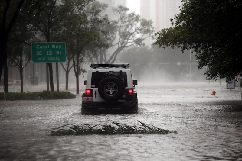 A vehicle drives along a flooded street in downtown Miami.