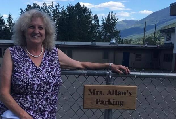 Retired teacher Doreen Allan at the parking space dedicated to her at Raft River Elementary School in Clearwater, B.C. (Submitted by Doreen Allan - image credit)