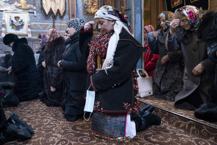 "Dr. Viktoria Mahnych, wearing a Hutsul's traditional colorful clothes, crosses herself holding a face mask in her hand because other worshippers forced her to take off her mask "" in order not to remind about the contagion"" in the Holy Trinity church during the Orthodox Christmas celebration in Iltsi village, Ivano-Frankivsk region of Western Ukraine, Thursday, Jan. 7, 2021. Mahnych fears that a lockdown in Ukraine came too late and the long holidays, during which Ukrainians frequented entertainment venues, attended festive parties and crowded church services, will trigger a surge in new coronavirus infections. (AP Photo/Evgeniy Maloletka)"