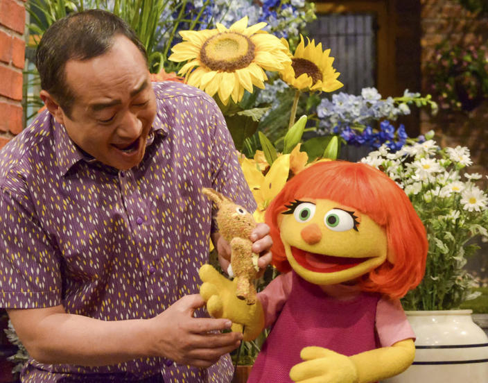 """This image released by Sesame Workshop shows castmember Alan Muraoka, left, with Julia, an autistic muppet character debuting on the 47th Season of """"Sesame Street."""" The popular children's TV show is celebrating its 50th season. (Zach Hyman/Sesame Workshop via AP)"""