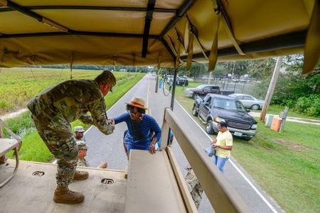 U.S. Army Brig. Gen. Jeff Jones, the South Carolina National Guard Assistant Adjutant General for Army, assists soldiers as they transport community members into flooded areas to retrieve critical items from their homes as the water continues to rise as a result of Hurricane Florence in their neighborhoods, in the town of Bucksport, South Carolina, U.S. September 24, 2018. Staff Sgt. Jorge Intriago/U.S. Army National Guard/Handout via REUTERS
