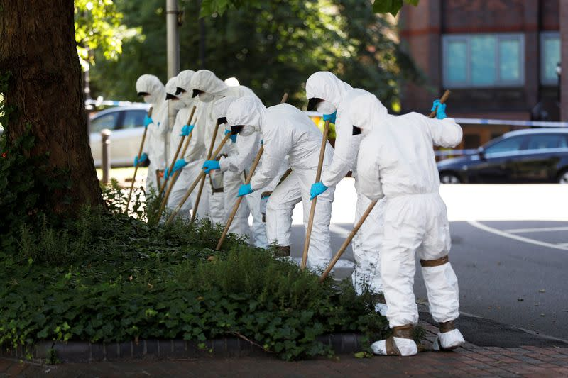 Forensic officers search near the scene of reported multiple stabbings in Reading