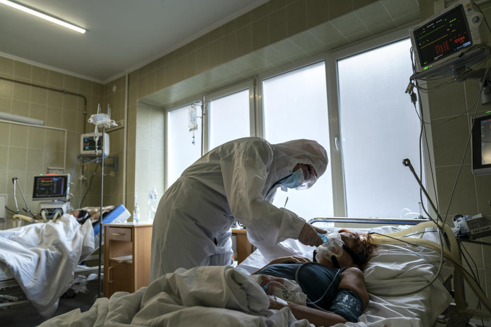 A nurse wearing a special suit to protect herself against coronavirus, treats a patient with COVID-19 in the ICU department of the emergency hospital in Lviv, Western Ukraine, Saturday, Jan. 9, 2021. Ukraine imposed a broad lockdown Friday, but many medical workers in the country fear that it came too late and the long holidays, during which Ukrainians frequented entertainment venues, attended festive parties and crowded church services, will trigger a surge in new coronavirus infections. (AP Photo/Evgeniy Maloletka)