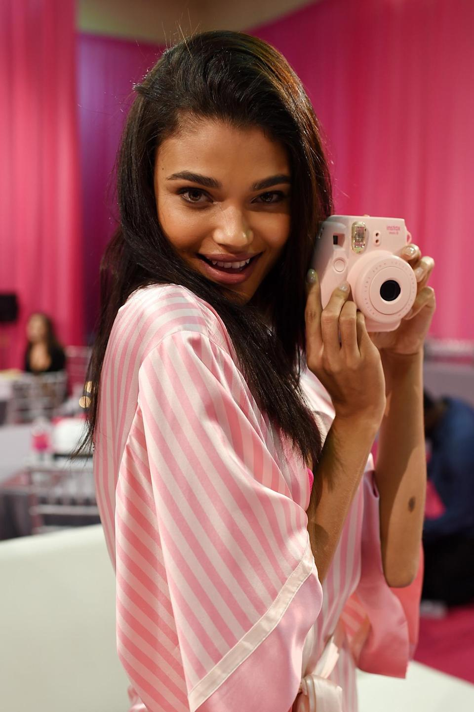 <p>Brazilian Daniela Braga takes a photo with a pink camera while wearing a pink and white robe while someone else takes a picture of her with yet another camera. </p>