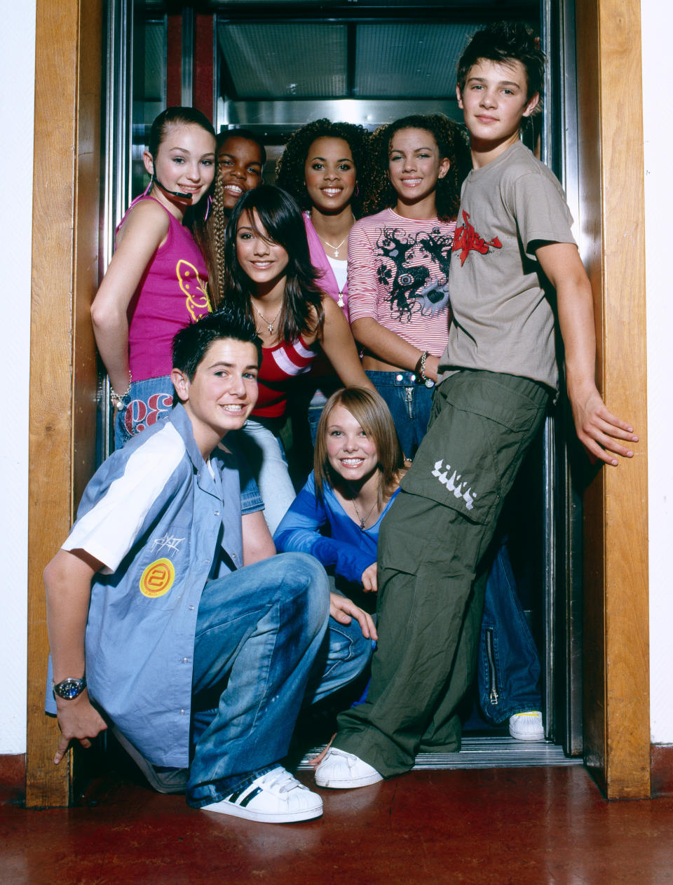 S Club Juniors backstage at a TV show, London, circa 2002. Left to right (back) Daisy Evans, Jay Asforis, Frankie Sandford, Rochelle Wiseman, Stacey McClean, Calvin Goldspink, (kneeling) Aaron Renfree, Hannah Richings. (Photo by David Tonge/Getty Images)