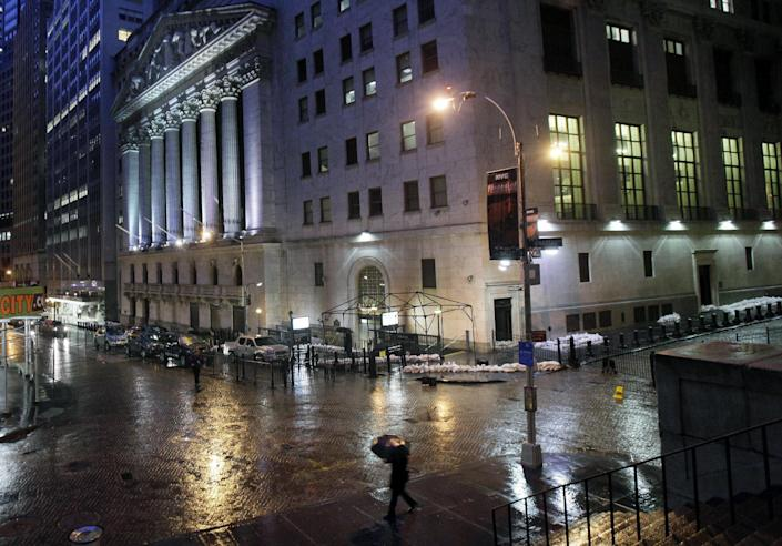 Sand bags protect the front of the New York Stock Exchange, Monday, Oct. 29, 2012. Hurricane Sandy continued on its path Monday, forcing the shutdown of mass transit, schools and financial markets, sending coastal residents fleeing, and threatening a dangerous mix of high winds and soaking rain. There had been plans to allow electronic trading to go forward on the New York Stock Exchange but with a storm surge expected to cover parts of lower Manhattan in water, officials decided late Sunday that it was too risky to ask any personnel to staff the exchanges. (AP Photo/Richard Drew)