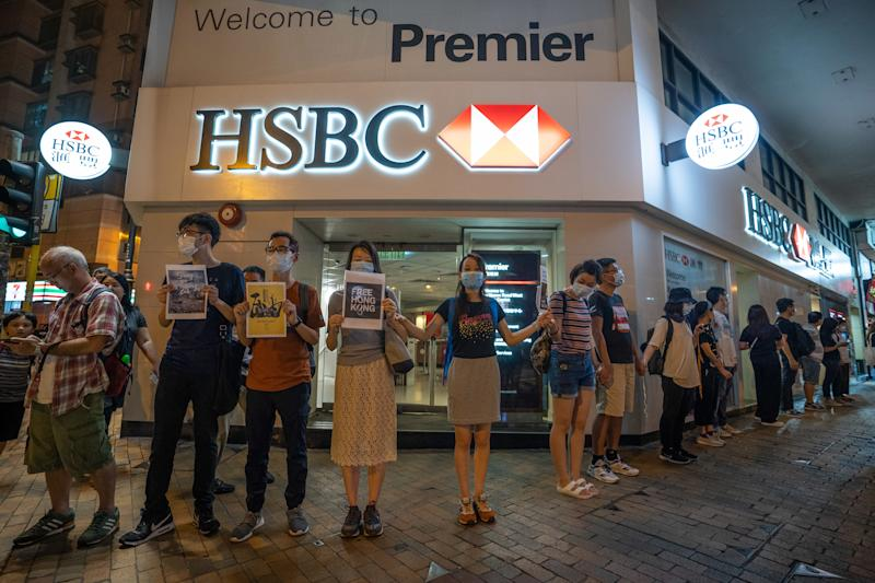 "HONG KONG, CHINA - 2019/08/23: Protesters form a human chain in front of a HSBC bank branch. Thousands of Hong Kong protesters link hands to form human chain across the city to call for democracy during the Hong Kong way event. The chains, which traced three subway routes, totaled around 40 kilometers (25 miles) in length. The protesters said they were inspired by the ""Baltic Way', when millions created a chain across three countries (Estonia, Latvia and Lithuania) to protest Soviet occupation exactly 30 years ago, and is the latest in the nearly 11-week-old movement that began with calls to scrap a now-suspended extradition bill and has broadened to include demands for full democracy and an independent inquiry into alleged police brutality. (Photo by Geovien So/SOPA Images/LightRocket via Getty Images)"
