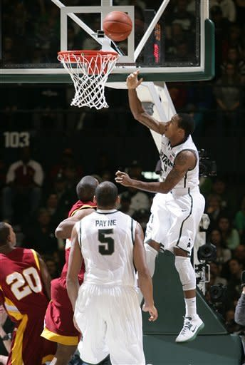 Michigan State's Keith Appling, right, shoots a layup against Tuskegee's Adrian Spellman, center, as Michigan State's Adreian Payne (5) and Camden Foster (20) watch during the first half of an NCAA college basketball game, Saturday, Dec. 15, 2012, at Jenison Field House in East Lansing, Mich. (AP Photo/Al Goldis)