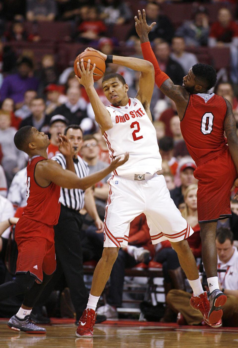 Ohio State's Marc Loving (2) rebounds between Miami's Eric Washington (33) and Geovonie McKnight (0) during the second half of an NCAA college basketball game, Monday, Dec. 22, 2014, in Columbus, Ohio. Ohio State won 93-55. (AP Photo/Mike Munden)